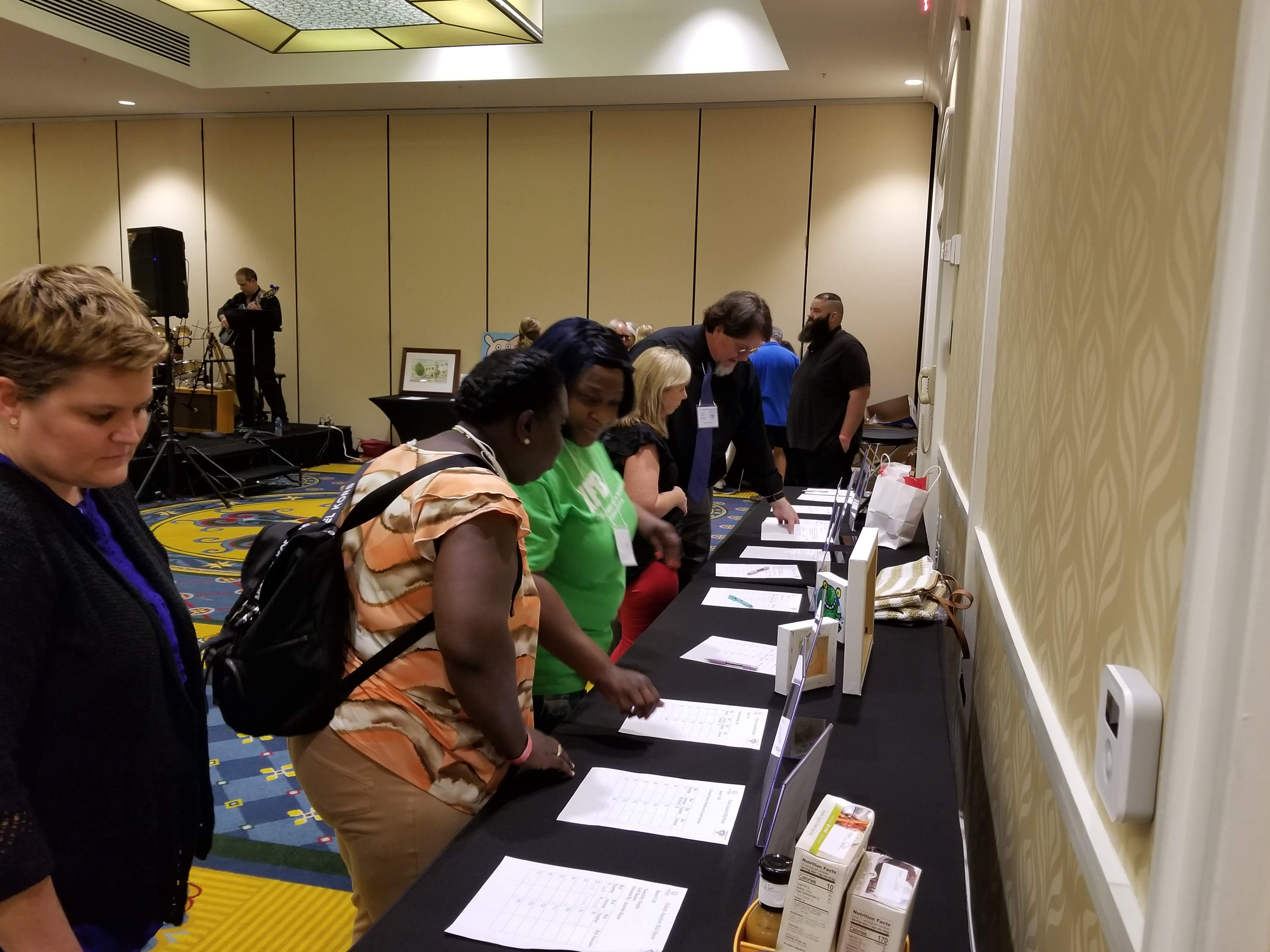 overview of people looking over silent auction items